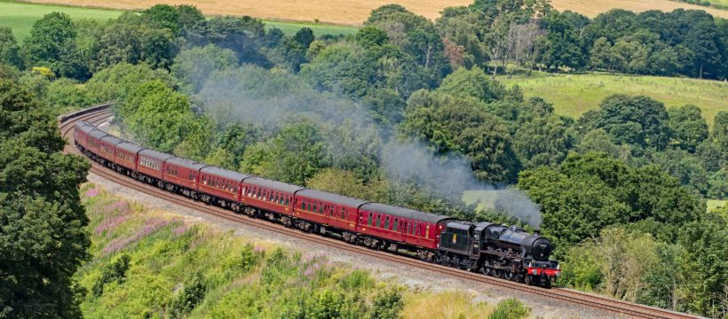 """Cumbria has seen a typical British summer with cloud and occasional rain. On 13 July 2019 in a rare patch of good light, former LMS Stanier """"Jubilee"""" 45690 """"Leander"""", looking every inch the late 1950s and reunited with her original tender, powers around Armathwaite curve on the Settle – Carlisle line as she heads south with train 1Z87, the 14.12 Carlisle – Carnforth leg of the Euston bound """"Cumbrian Mountain Express""""."""