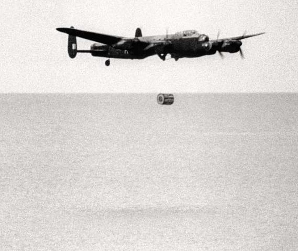 Film still of a 617 Squadron Lancaster B.III (Special) practice dropping an Upkeep at Reculver on 12 May 1943. The bomb is caught just falling from the Lancaster which can be seen beginning to climb. IWM FLM2340