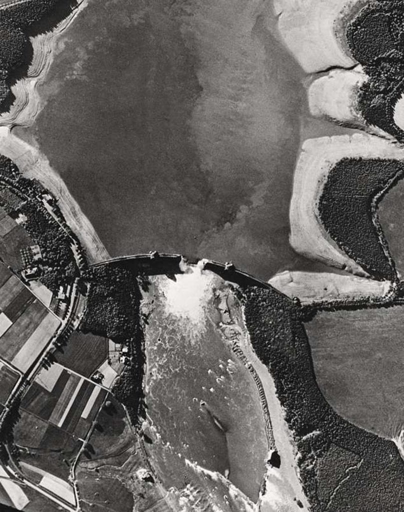 Aerial reconnaissance picture taken on 17 May 1943 clearly showing the breach in the Möhne Dam, water still gushing through and the by then largely drained reservoir. Crown Copyright