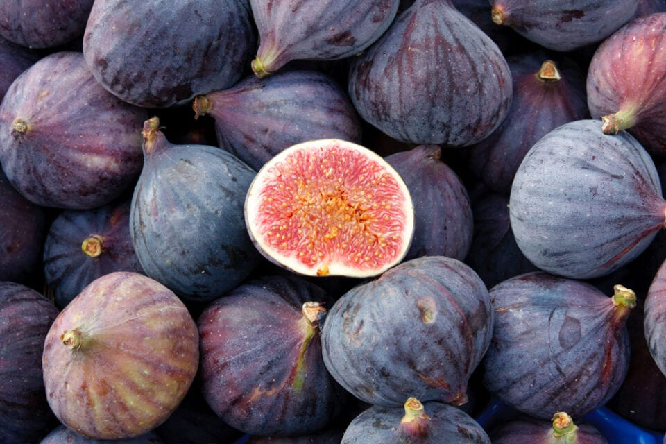 Lots of figs with one half fig showing the inside on top.