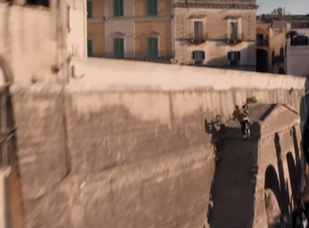 Side of an old wall - check. Motocross bike - check. Stuntman with a camera helicopter chasing him - check. Right people, let's get this done. Nice and high please, chap...