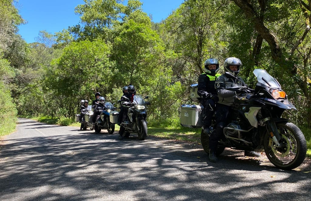 The group sit in pairs on their bikes as they ride along a forest road.