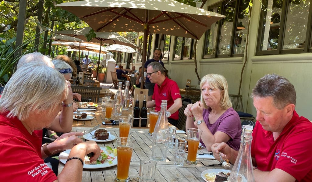 The group have lunch at a restaurant outdoors.